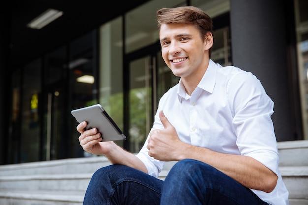 ビジネスセンターの近くでタブレットを使用して陽気な青年実業家