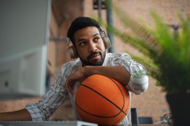 ヘッドフォンとボールでオフィスで休憩し、休んでいる陽気な青年実業家。