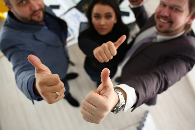 Cheerful young businessmen have success results show big fingers