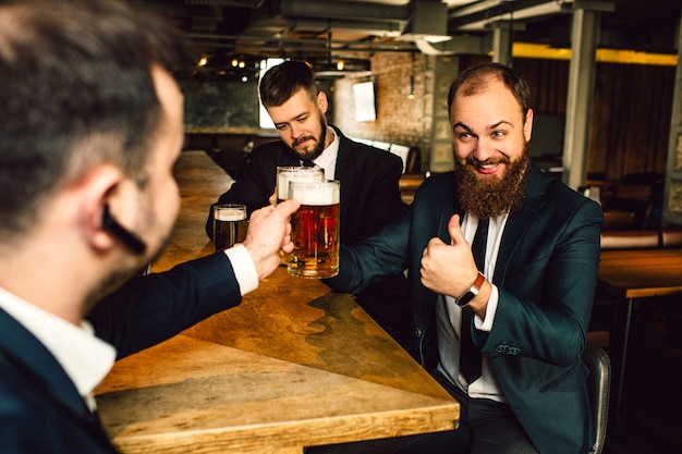 Cheerful young businessmen sit at table. they hold mugs of bear. bearded guy hold big thumb up.