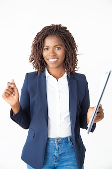 Cheerful young businesswoman holding clipboard