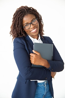 Cheerful young businesswoman holding folder