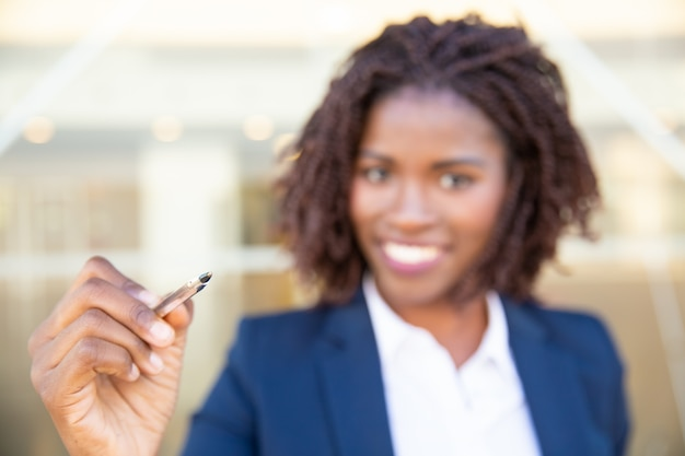 Cheerful young businesswoman holding pen