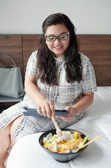 ベッドに座って、タブレットコンピューターで電子メールや記事を読んだり、フルーツサラダを食べたりする陽気な若い実業家