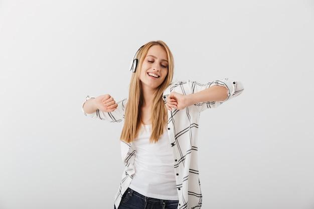 Веселая молодая случайная женщина слушает музыку в наушниках