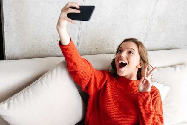 Cheerful young casually dressed woman sitting on a couch at home, taking a selfie
