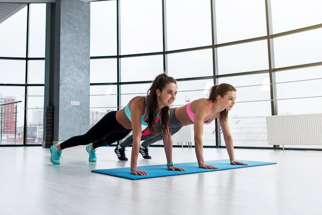 Cheerful young caucasian girlfriends doing push up exercise in light city fitness center