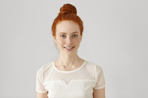 Cheerful young caucasian woman with freckles and ginger hair in bun