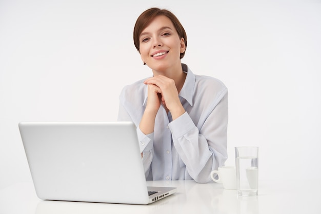 陽気な若い魅力的な茶色の髪の女性と短い流行のヘアカットは心地よく笑って、彼女のあごの下に手を保ち、白の上に座っています