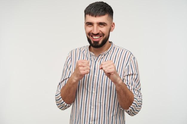 陽気な若い魅力的な黒髪のひげを生やした男は、彼の拳を上げて、カジュアルなシャツの白い壁に隔離された広い笑顔で幸せそうに見えます