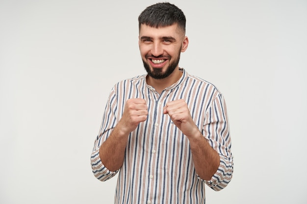 Cheerful young charming dark haired bearded man keeping his fists raised and looking happily  with wide smile, isolated over white wall in casual shirt