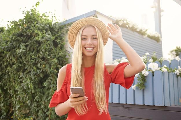 晴れた日に緑豊かな庭園の上に立って、広い笑顔でカメラを喜んで見ながら、彼女のストラップの帽子に手を上げる陽気な若い魅力的な白い頭の女性