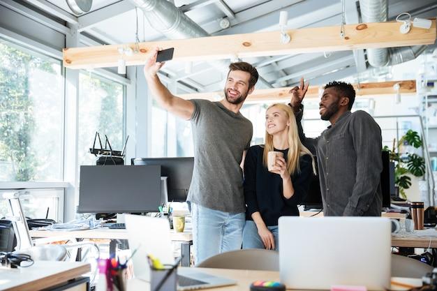 Веселые молодые коллеги в офисе коворкинг делают селфи