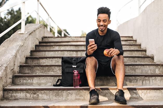 黒のショートパンツとtシャツを着た陽気な若いクールな浅黒い肌のスポーツマンが階段に座って、笑顔で、リンゴと電話を持っています