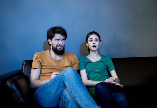 Веселая молодая пара дома смотрит телевизор, вечерний отдых у корня