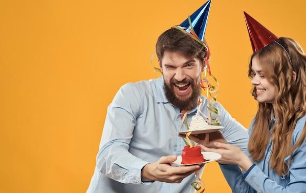 陽気な若いカップルの誕生日のお祝いの楽しいケーキ。高品質の写真