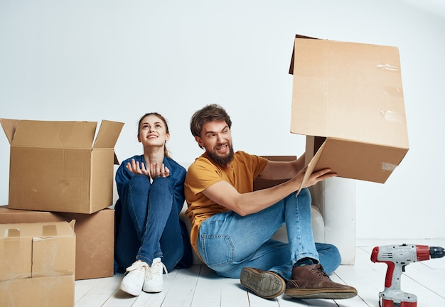 Cheerful young couple boxes with things new housing family