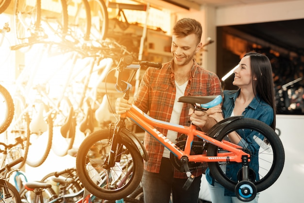 Cheerful young couple chooses kids bicycle in store.
