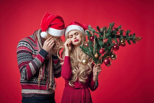 陽気な若いカップルのクリスマスの服の休日の装飾のおもちゃ