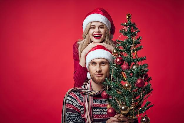 陽気な若いカップルのクリスマスの装飾のおもちゃ新年。高品質の写真