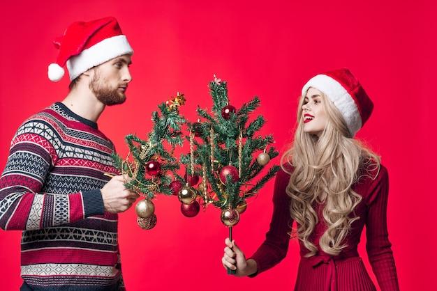 陽気な若いカップルのクリスマス休暇の赤い背景の装飾
