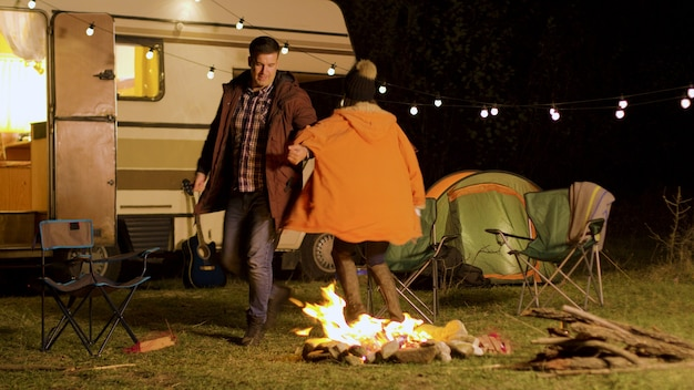 Cheerful young couple dancing around camp fire in cold night of autumn. retro camper van. camping tent.
