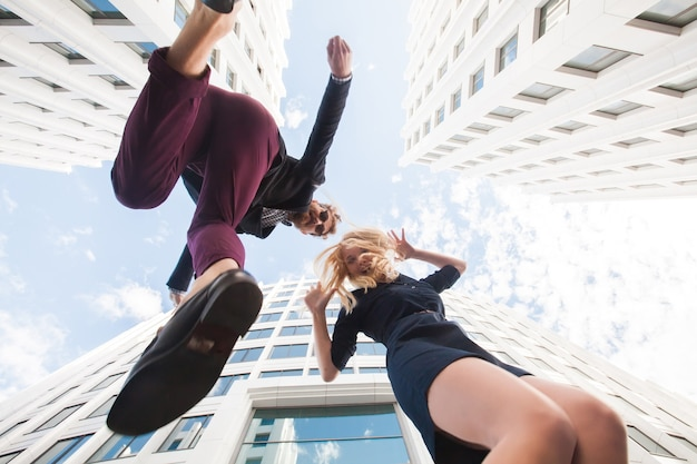 Cheerful young couple fooling around, jumping on the background of the building. bottom view