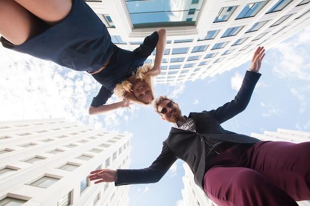 Веселая молодая пара дурачится, прыгая на фоне здания. вид снизу