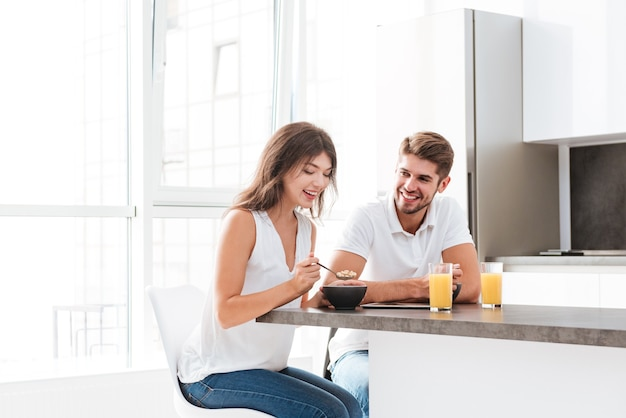 Cheerful young couple having breakfast on the kitchen at home