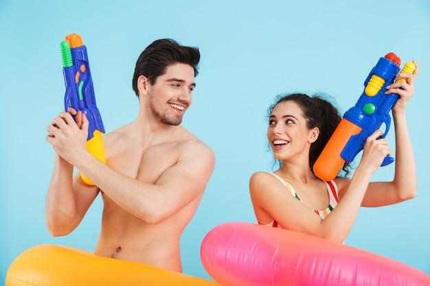 孤立したインフレータブルリングを身に着けて、水鉄砲で遊んで、ビーチで楽しんでいる陽気な若いカップル