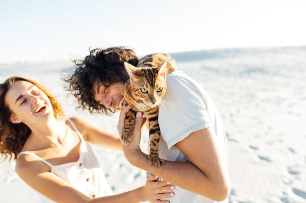 Веселая молодая пара веселится на пляже со своей бенгальской кошкой.