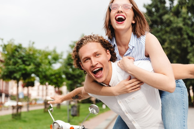 Cheerful young couple having fun together with scooter and looking at the camera while being in park