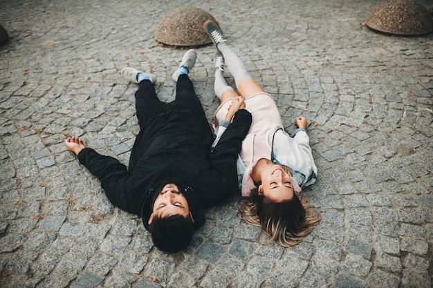 Веселая молодая пара, взявшись за руки и лежа на мощеной мостовой на улице