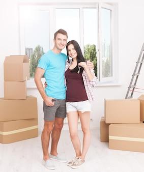 Веселая молодая пара держит ключи от своего нового дома