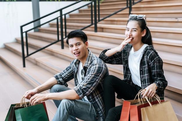 複数の紙の買い物袋を保持している陽気な若いカップル