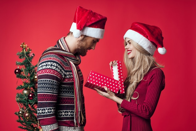 陽気な若いカップルの休日のクリスマスプレゼントの装飾の赤い背景