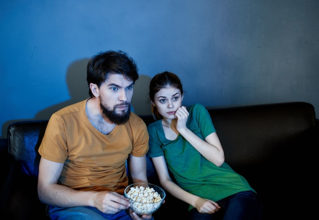 Cheerful young couple at home watching tv evening relaxation at the root