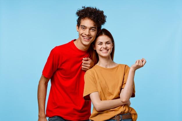 Cheerful young couple hugs communication fun fashion