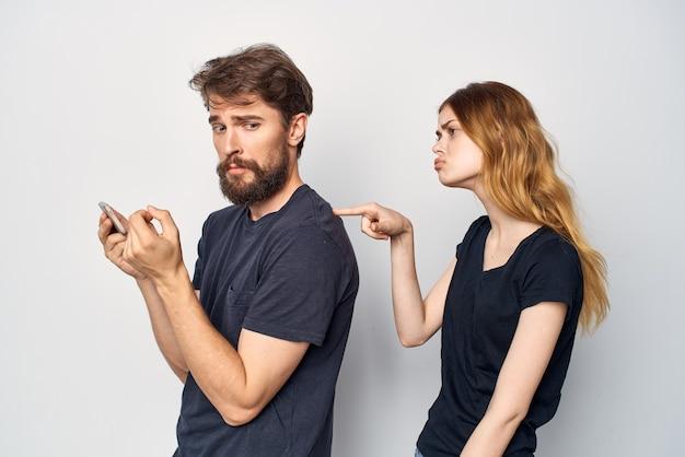 黒のtシャツを着た陽気な若いカップルは、友情スタジオライフスタイルと一緒に楽しい電話をかけます。高品質の写真