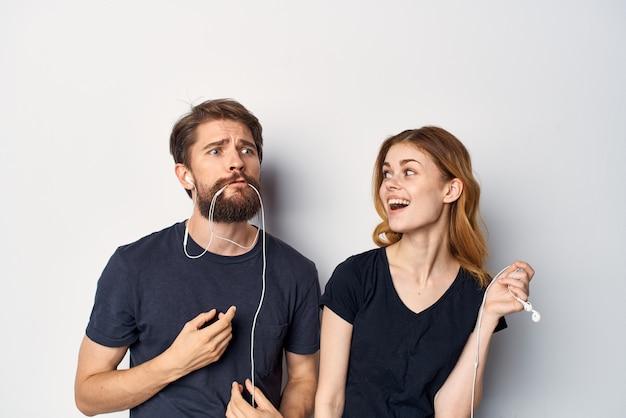 Веселая молодая пара в черных футболках по телефону весело вместе, дружба, студия, образ жизни