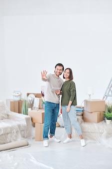 Веселая молодая пара в повседневной одежде обсуждает, где поставить новую мебель или телевизор, стоя в центре гостиной