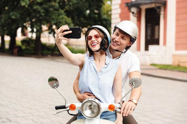 屋外のスクーターに一緒に座っている間スマートフォンでselfieを作るクラッシュヘルメットの陽気な若いカップル