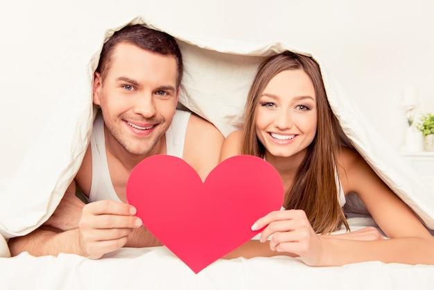 Веселая молодая влюбленная пара держит красное бумажное сердце