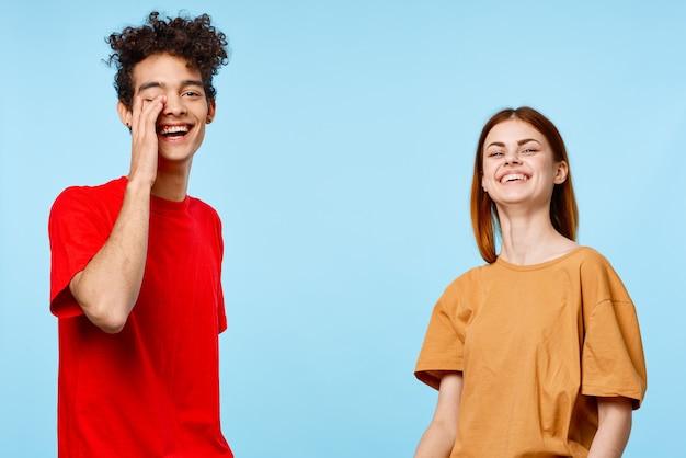 Веселая молодая пара в разноцветных футболках коммуникационная студия синем фоне