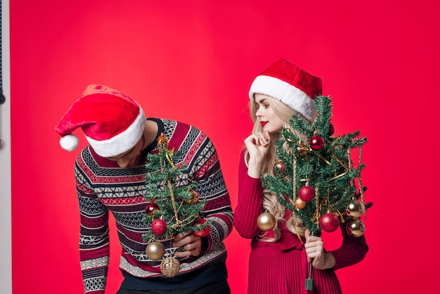 새해 옷 장식 장난감 빨간색 배경에 쾌활한 젊은 부부