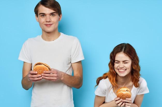 楽しいファーストフードのハンバーガーを持っている白いtシャツの陽気な若いカップル
