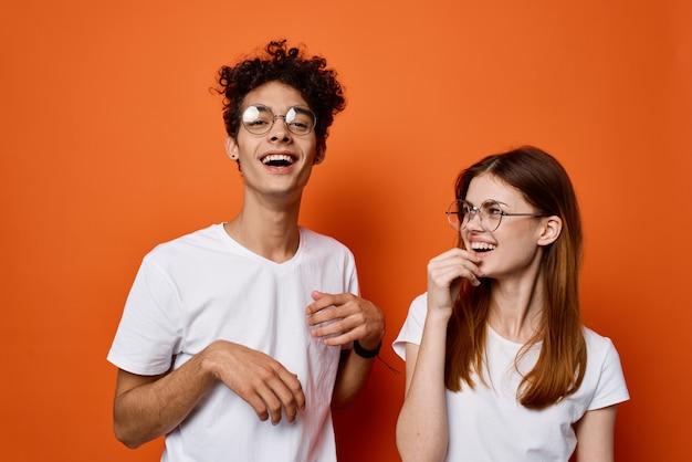 オレンジ色の背景にポーズをとって白い t シャツを着た陽気な若いカップル