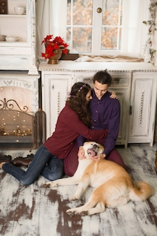Cheerful young couple is hugging and kissing a dog of akita inu breed. in christmas decorations in retro style