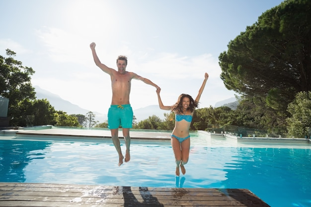 Cheerful young couple jumping into swimming pool