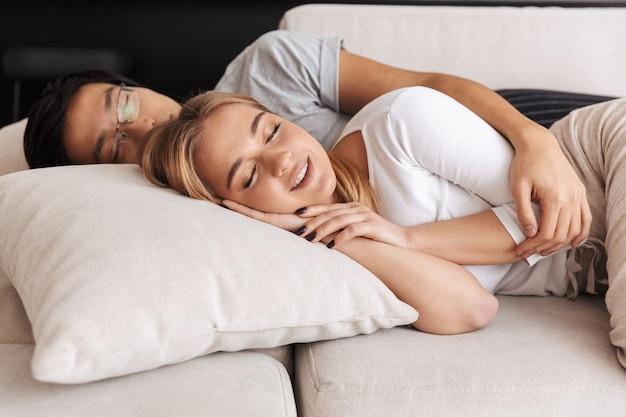 Веселая молодая пара, лежа на диване у себя дома, обнимаются